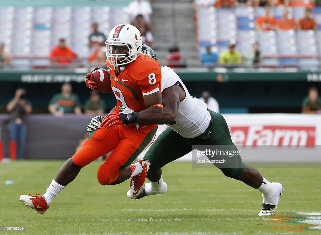 Duke Johnson #8 of the Miami Hurricanes is tackled by Sam Barrington #36 of the South Florida Bulls on November 17, 2012 at Sun Life Stadium in Miami Gardens, Florida. The Hurricanes defeated the Bulls 40-9.