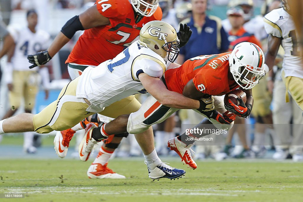 Duke Johnson #8 of the Miami Hurricanes is tackled by Tyler Stargel #47 of the Georgia Tech Yellow Jackets on October 5, 2013 at Sun Life Stadium in Miami Gardens, Florida. The Hurricanes defeated the Yellow Jackets 45-30.