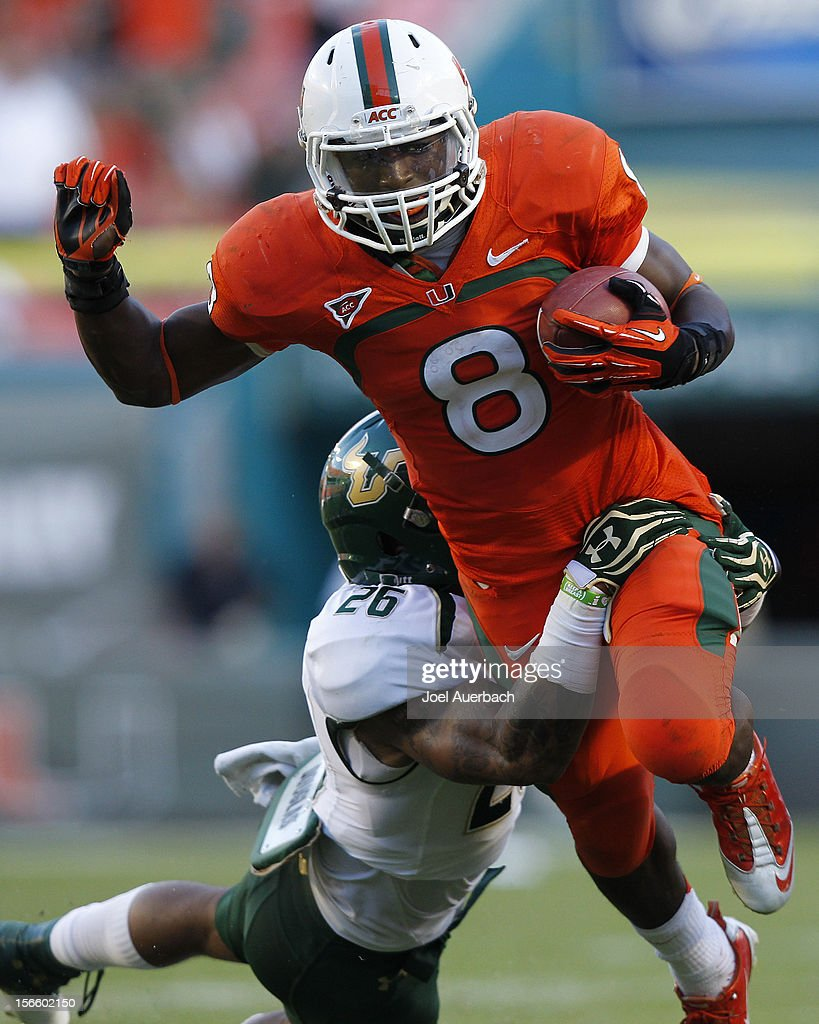 Duke Johnson #8 of the Miami Hurricanes runs with the ball and is tackled by Mark Joyce #26 of the South Florida Bulls on November 17, 2012 at Sun Life Stadium in Miami Gardens, Florida. The Hurricanes defeated the Bulls 40-9.