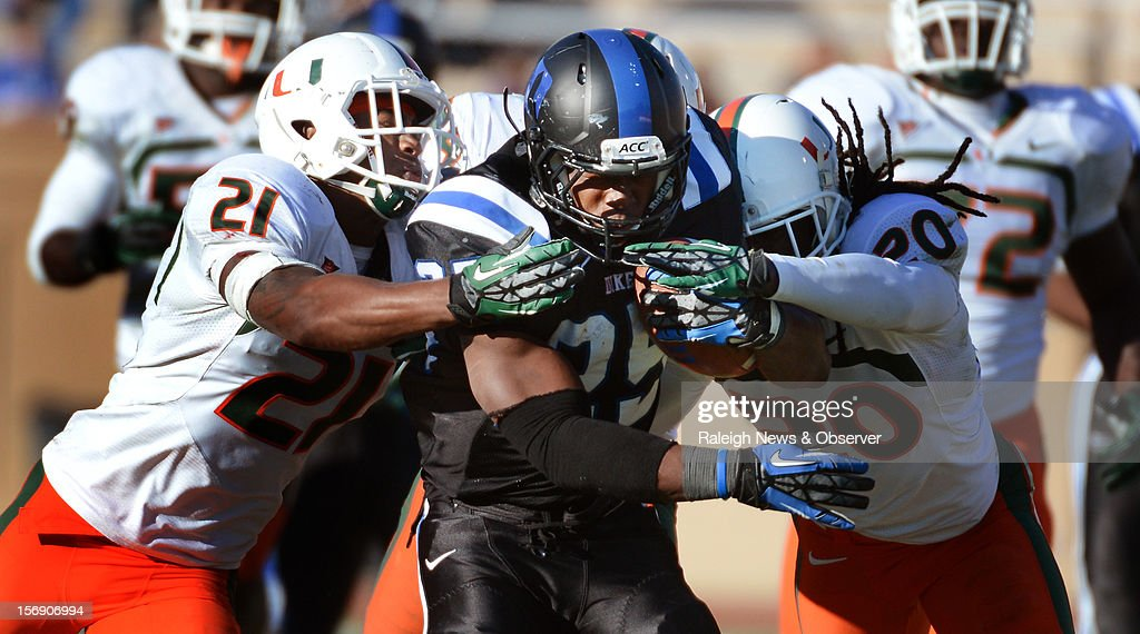 Duke running back Jela Duncan (25) runs for a 37-yard gain in the first half against Miami defensive back Brandon McGee (21) and teammate defensive back Thomas Finnie (20) at Wallace Wade Stadium on Saturday, November 24, 2012, in Durham, North Carolina. The Miami Hurricanes defeated the Duke Blue Devils, 52-45.