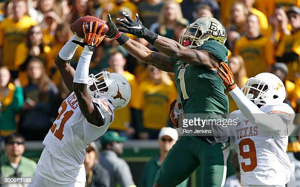 Duke Thomas of the Texas Longhorns intercepts against Corey Coleman of the Baylor Bears as Texas' Davante Davis looks on in the second quarter at...
