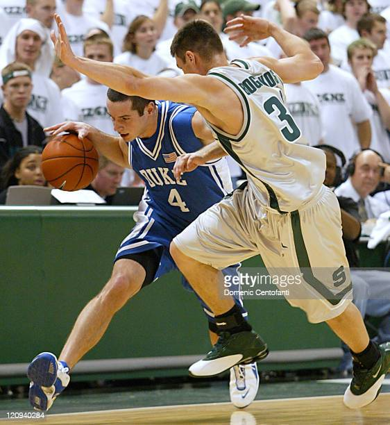 Duke's JJ Redick rushes the ball upcourt along the sideline in the second half while Spartan Tim Bograkos plays hard defense