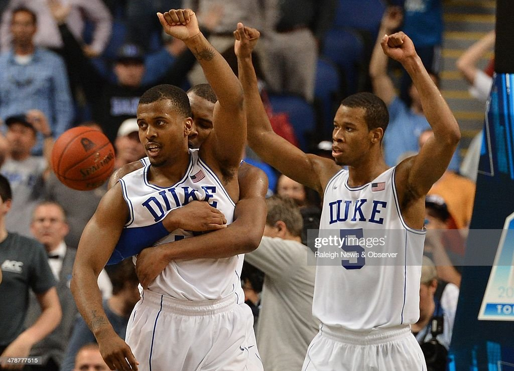 Duke's Rasheed Sulaimon (14) embraces teammate Tyler Thornton (3) as time expires and Duke escapes with a 63-62 victory against Clemson in the ACC Tournament quarterfinals at the Greensboro Coliseum in Greensboro, N.C., Friday, March 14, 2014.