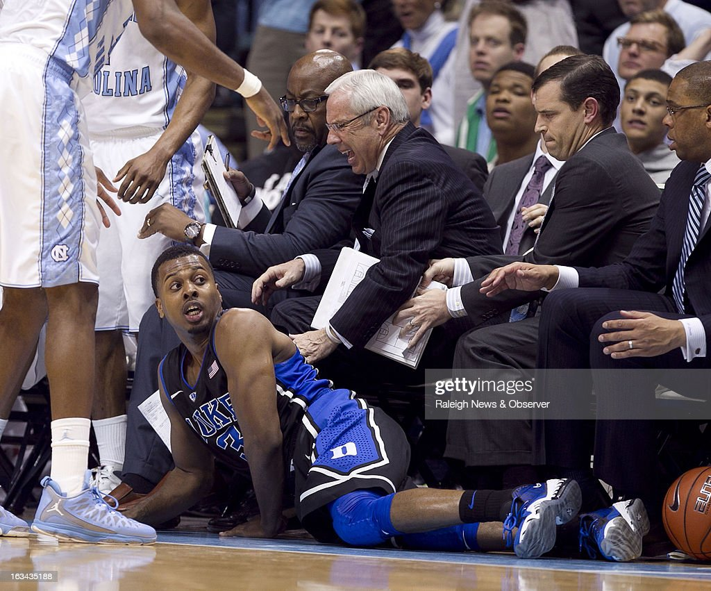 Duke's Tyler Thornton (3) dives into North Carolina coach Roy Williams and the Tar Heels' bench in pursuit of a loose ball in the second half on Saturday, March 9, 2013, at the Smith Center in Chapel Hill, North Carolina. Duke topped the Tar Heels, 69-53.