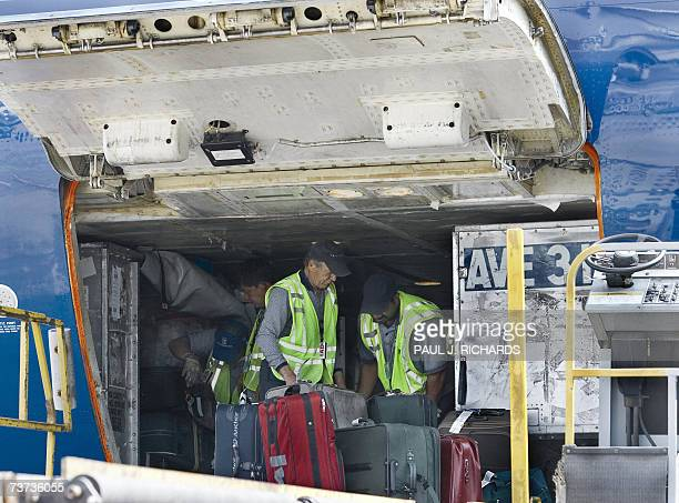 Ground crew members work inside the cargo hold of United Airlines flight shortly before lift off from Washington DC's Dulles International Airport on...