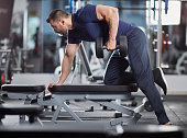 Man doing dumbbell row for back workout in the gym