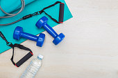 dumbbells, exercise equipment, gym yoga mat, and bottle of water on clean wood floor, healthy and well being concept, with room for text or copy space