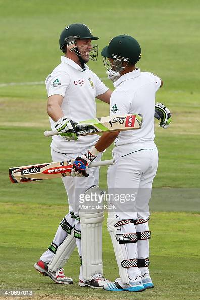 Duminy of South Africa congratulates his teammate AB de Villiers after De Villiers passed 100 runs during day two of the Second Test match between...