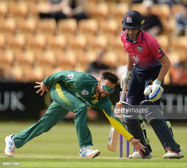 Duminy of South Africa tries to stop a ball as Max Holden of Northamptonshire looks on during the oneday match between Northamptonshire and South...
