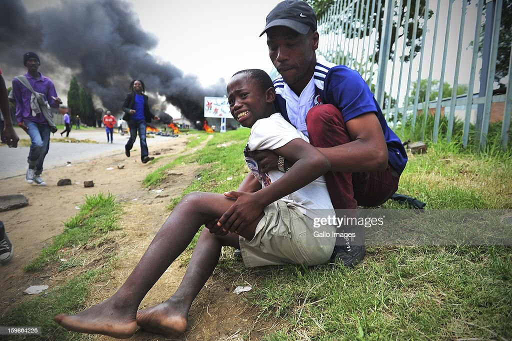 Dumisani Mthimkhulu is hit by a rubber bullet on his leg on January 20, 2013, in Sasolburg, South Africa. Residents of the Zamdela township took to an illegal march after the announcement of the changing of all municipal systems from Sasol to Parys.