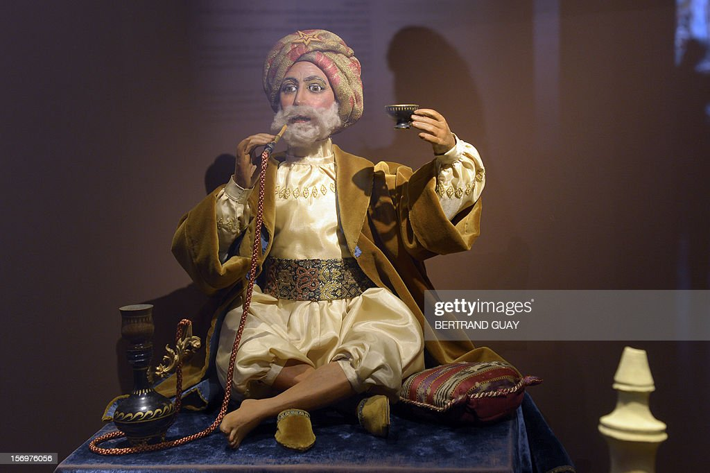 A dummy is displayed smoking shisha and drinking tea during the exhibition entitled 'Les Mille et une Nuits' (The thousand and one nights) at the Arab World Institute (IMA) on November 26, 2012 in Paris. The event runs until April 28, 2013. AFP PHOTO/ BERTRAND GUAY