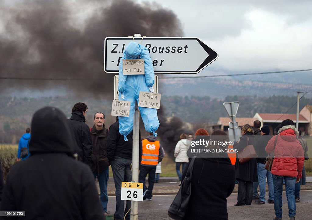 A dummy with signs reading 'Montebourg killed me', 'Atmel sold me', and GMBH stole me' remains hanging from a road sign as workers of semiconductor manufacturer LFoundry block the access to the Industrial Zone in Rousset, near Aix-en-Provence, southern France, on December 23, 2013, after trade unions announced that a court had ordered a judicial liquidation of their factory. Over 670 jobs are at risk if the factory closes and approximately 400 workers took part in the protest and blocade of the Rousset industrial zone, as French Minister for Industrial Renewal Arnaud Montebourg prepared to receive a delegation of workers in Paris today. AFP PHOTO / BERTRAND LANGLOIS