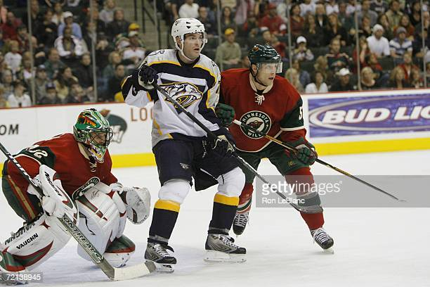 P Dumont of the Nashville Predators is pictured between goalie Niklas Backstrom and Nick Schultz of the Minnesota Wild during a game at Xcel Energy...