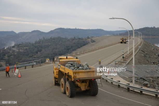 A dump truck carrying boulders makes its way onto the Oroville Dam as workers try to fix the damage below the emergency spillway at Oroville Lake on...