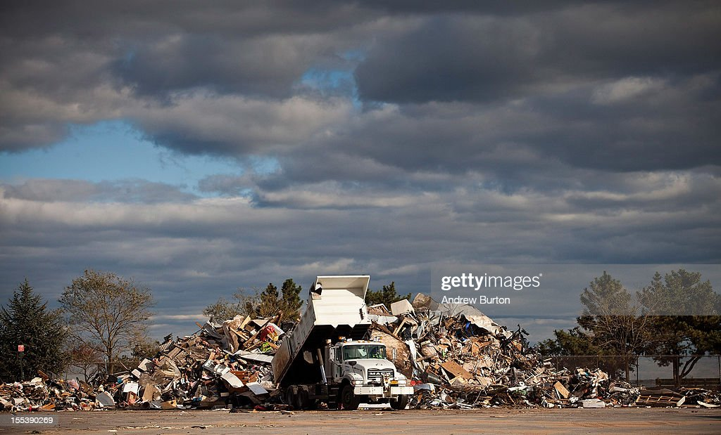 A dump truck empties trash collected from Superstorm Sandy damaged homes on November 3, 2012 in the Midland Beach neighborhood of Staten Island borough of New York City. With the death toll currently over 100 and millions of homes and businesses without power, the U.S. East Coast is attempting to recover from the effects of floods, fires and power outages brought on by Superstorm Sandy. New Jersey has begun rationing gas and the Department of Defense will be setting up mobile gas stations in New York City and Long Island.