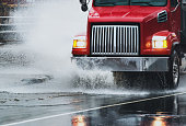 A dump truck navigates a flooded portion of highway after heavy rains.