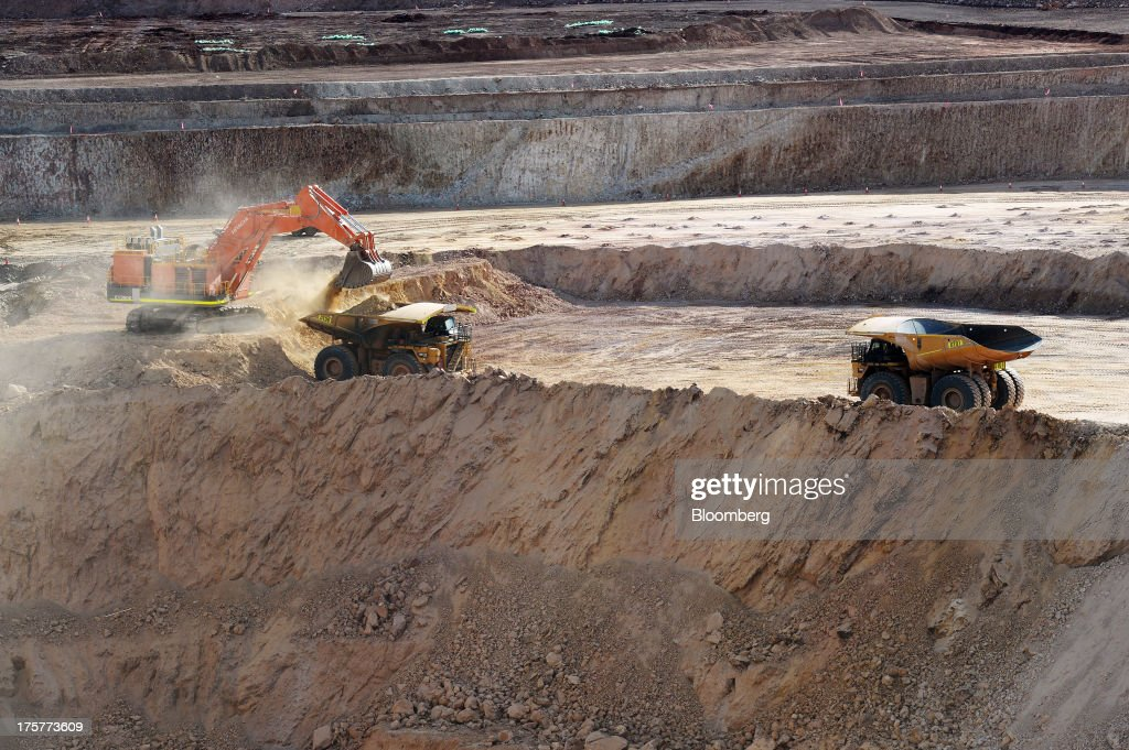 A dump truck is loaded with ore in the open-pit mine as another truck approaches at the Norton Gold Fields Ltd. Enterprise operations 68 kilometers north-west of Kalgoorlie, Australia, on Wednesday, Aug. 7, 2013. Norton, the Australian producer controlled by China's Zijin Mining Group Co., is seeking further acquisition targets as falling prices cut the value of mines. Photographer: Carla Gottgens/Bloomberg via Getty Images