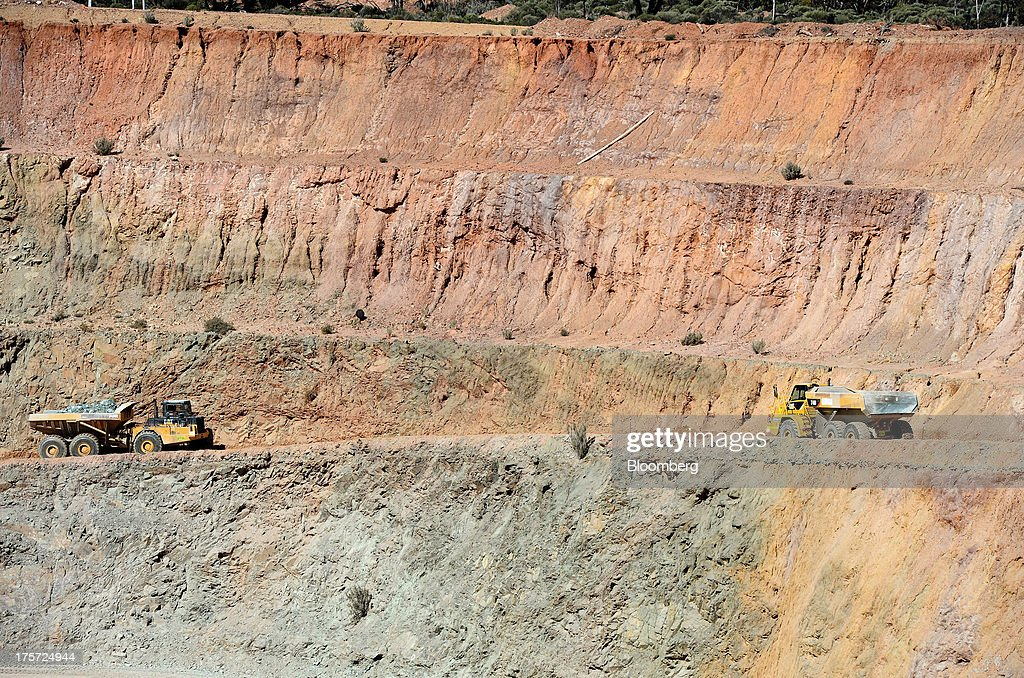 A dump truck, left, transports ore from the mine pit at the Phoenix Gold Ltd. Castle Hill gold project in Kunanalling, northwest of Kalgoorlie, Australia, on Tuesday, Aug. 6, 2013. Gold prices will rebound as output remains little changed or declines this year with producers cutting spending and shuttering some costly operations, the World Gold Council said. Photographer: Carla Gottgens/Bloomberg via Getty Images