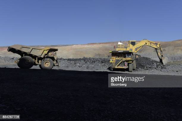 A dump truck left waits to move into position as an excavator deposits ore into another dump truck at the White Foil open pit mine at Evolution...