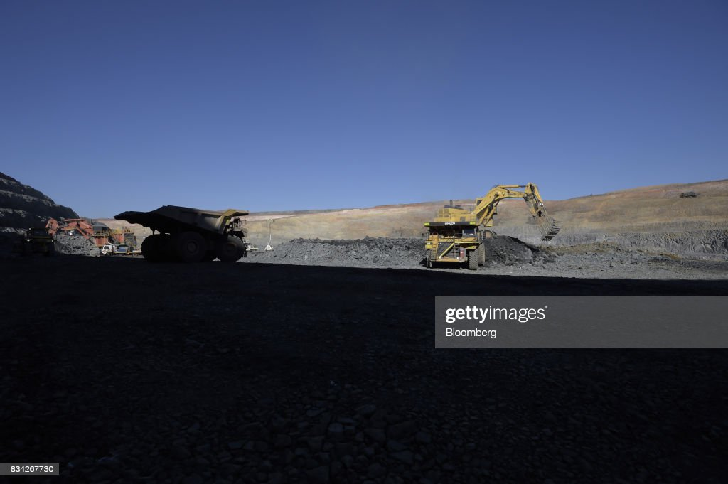 A dump truck, left, waits to move into position as an excavator deposits ore into another dump truck at the White Foil open pit mine at Evolution Mining Ltd.'s gold operations in Mungari, Australia, on Tuesday, Aug. 8, 2017. Evolution Mining is Australias second-largest gold producer. Photographer: Carla Gottgens/Bloomberg via Getty Images
