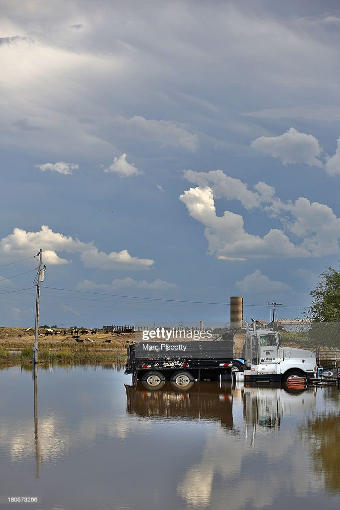 A dump truck sits in standing flood water from the South Platte River on September 14, 2013 in La Salle, Colorado. Heavy rains for the better part of week fueled widespread flooding in numerous Colorado towns. The historic flooding forced thousands to evacuate the area and more rain is predicted through the weekend.