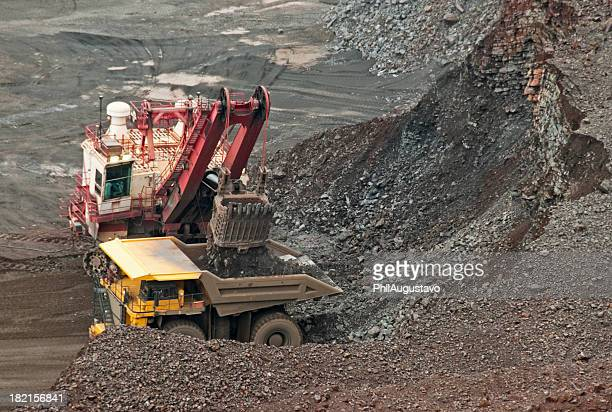 Dump truck taking load of iron ore from crane shovel