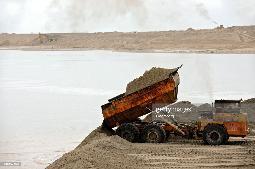 A dump truck tips sand into the sea for land reclamation at the construction site of Dialog Group Bhd.'s new storage terminal in Pengerang, Johor, Malaysia, on Tuesday, Dec. 18, 2012. Dialog, Malaysia's second-biggest oil and gas services provider, said it signed some customers for the 1.9 billion-ringgit ($620 million) storage terminal it's developing with Royal Vopak NV. Photographer: Munshi Ahmed/Bloomberg via Getty Images