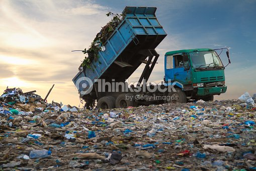 Dump Truck Unloading The Waste On A Open Dumping Site Stock Photo