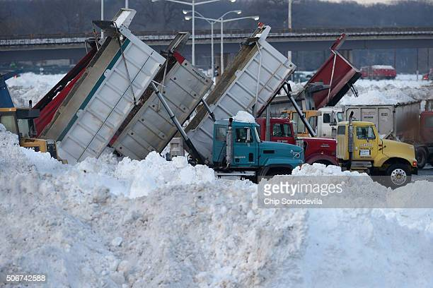 Dump trucks and excavators create a miniature mountain range of snow taken off the streets of the capital in one of the parking lots near Robert F...