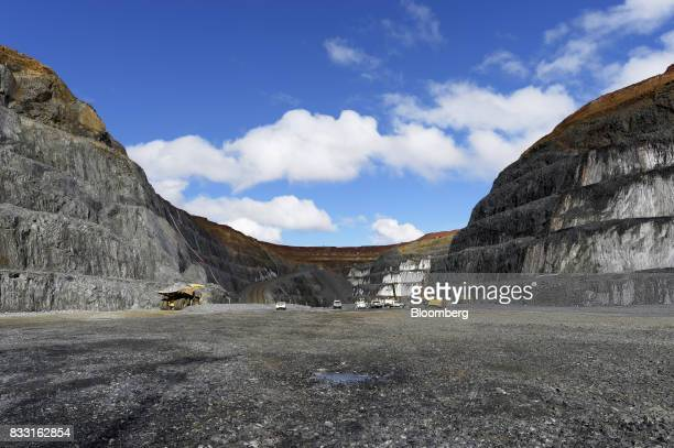 Dump trucks and excavators operate in the Invincible open pit mine at the St Ives Gold Mine operated by Gold Fields Ltd in Kambalda Australia on...