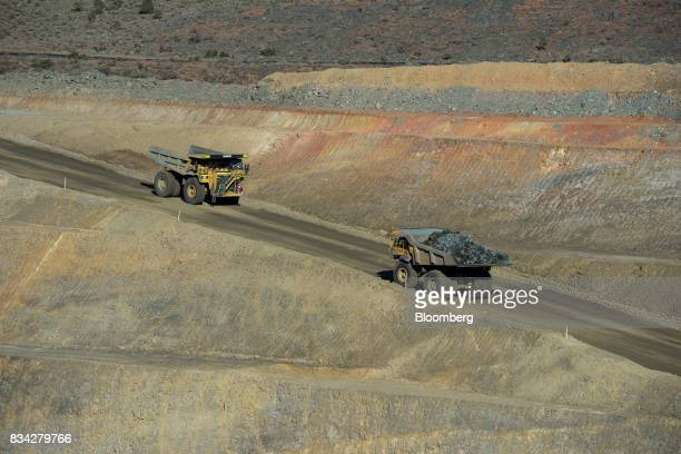 Dump trucks drive along an access ramp in the White Foil open mine pit at Evolution Mining Ltd's gold operations in Mungari Australia on Tuesday Aug...