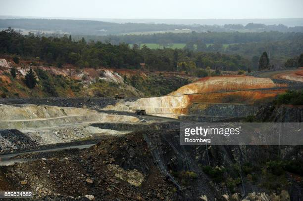 Dump trucks drive along an access ramp to an open pit mine at a Talison Lithium Ltd site a joint venture between Tianqi Lithium Corp and Albemarle...