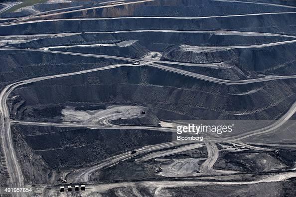 Dump trucks drive along haul roads in the Mt Owen mine at Glencore Plc's Mount Owen Complex coal operations in this aerial photograph taken near...