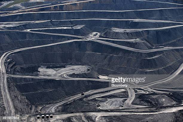 Dump trucks drive along haul roads in the Mt Owen mine at Glencore Plc's Mount Owen Complex coal operations in this aerial photograph taken near...