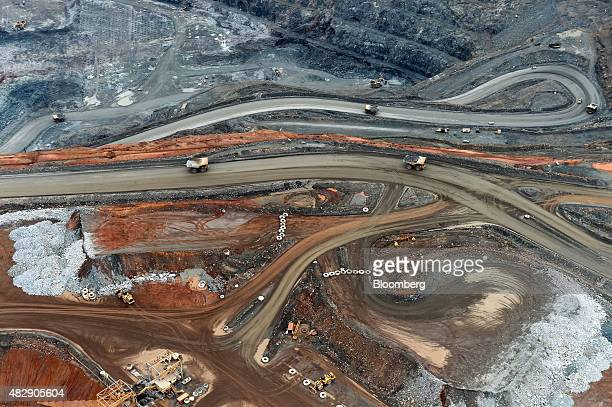 Dump trucks drive along haul roads inside the Fimiston Open Pit mine known as the Super Pit in this aerial photograph taken above Kalgoorlie...