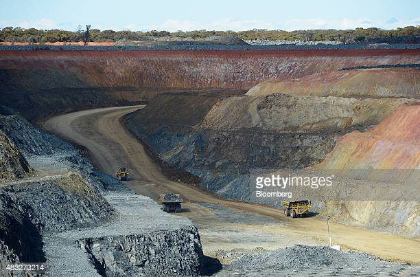 Dump trucks drive through the open mine pit at Evolution Mining Ltd's gold operations in Mungari Australia on Wednesday Aug 5 2015 A declining gold...