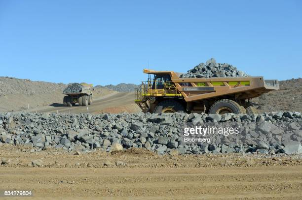 Dump trucks filled with ore drive out of in the White Foil open mine pit at Evolution Mining Ltd's gold operations in Mungari Australia on Tuesday...