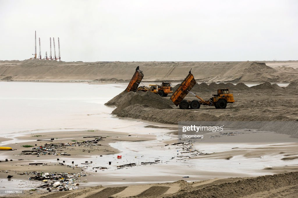 Dump trucks tip sand into the sea for land reclamation at the construction site of Dialog Group Bhd.'s new storage terminal in Pengerang, Johor, Malaysia, on Tuesday, Dec. 18, 2012. Dialog, Malaysia's second-biggest oil and gas services provider, said it signed some customers for the 1.9 billion-ringgit ($620 million) storage terminal it's developing with Royal Vopak NV. Photographer: Munshi Ahmed/Bloomberg via Getty Images