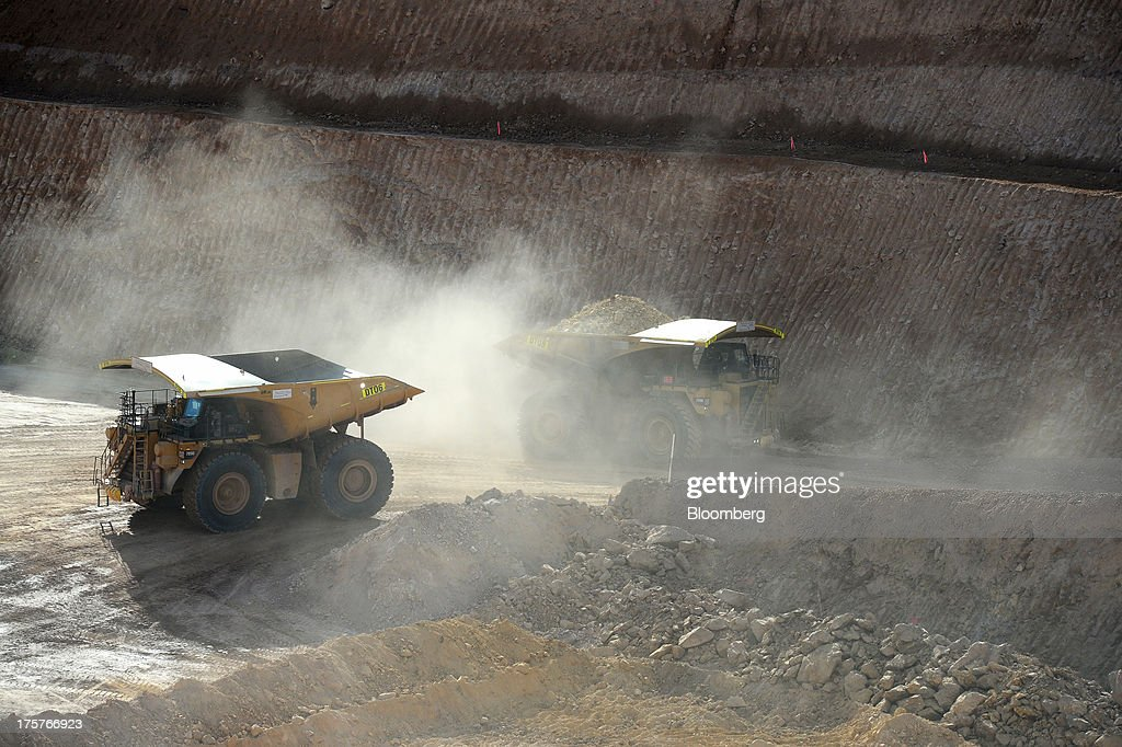 Dump trucks transport ore from the open mine pit at the Norton Gold Fields Ltd. Enterprise operations 68 kilometers north-west of Kalgoorlie, Australia, on Wednesday, Aug. 7, 2013. Norton, the Australian producer controlled by China's Zijin Mining Group Co., is seeking further acquisition targets as falling prices cut the value of mines. Photographer: Carla Gottgens/Bloomberg via Getty Images