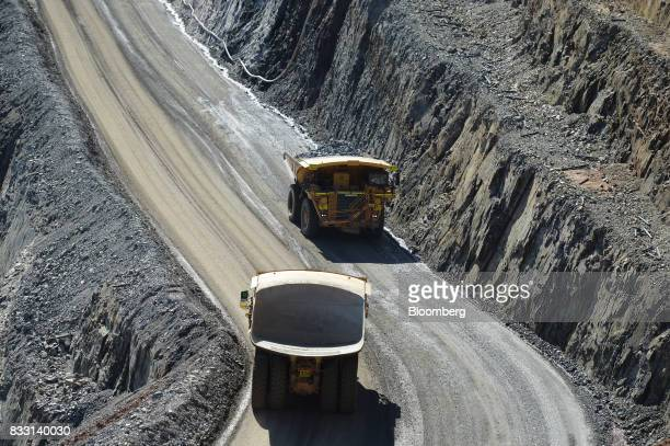Dump trucks travel along an access ramp of the Invincible mine at the St Ives Gold Mine operated by Gold Fields Ltd in Kambalda Australia on...