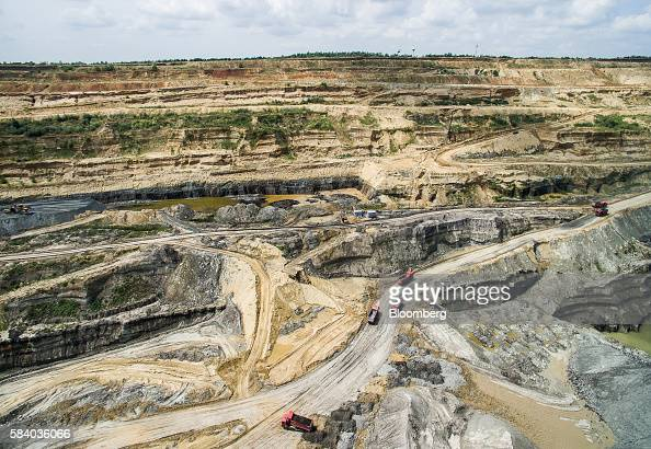 Dump trucks travel through the open pit at the Visonta open cast lignite mine operated by Matrai Eromu Zrt in Visonta Hungary on Wednesday July 27...