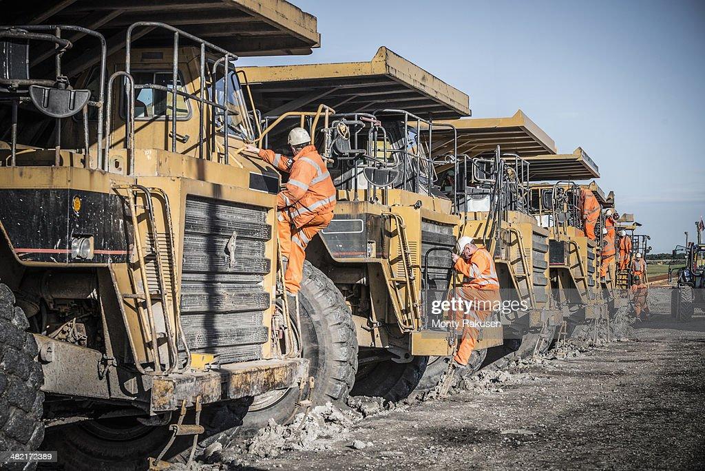 Dumper truck drivers climb down for break at surface coal mine