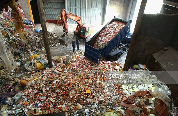 A dumper truck unloads as workers check through products made from US imported beef in front of trash burner on January 16 2004 in Incheon South...