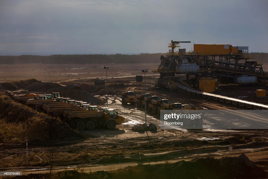 Dumper trucks, manufactured by Caterpillar Inc., sit parked beside a giant mining conveyor machine at an open-pit lignite mine operated by Vattenfall AB in Welzow-Sued, Germany, on Saturday, Jan. 11, 2014. Across the continent's mining belt, from Germany to Poland and the Czech Republic, utilities such as Vattenfall AB, CEZ AS and PGE SA are expanding open-pit mines that produce lignite. Photographer: Krisztian Bocsi/Bloomberg via Getty Images