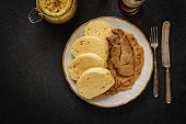 Czech traditional cuisine dumplings cabbage and pork meat and beer  on black stone table
