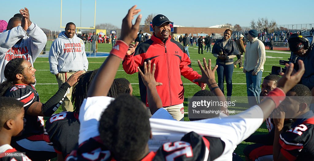 Dunbar's head coach Jerron Joe, center, has a cheer with his team after the win as Dunbar defeats Anacostia 12 - 8 in the Turkey Bowl at Eastern High School in Washington DC, November 22, 2012 .