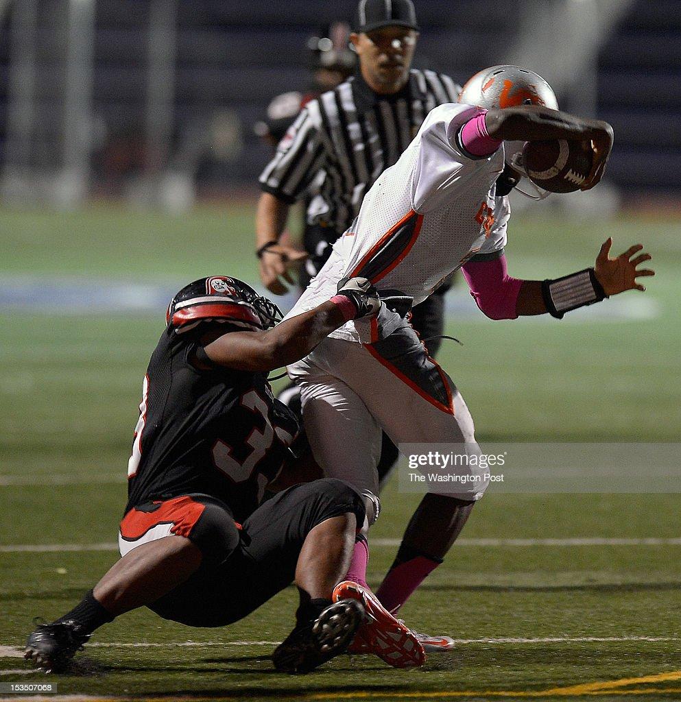 Dunbar's Johnathan Hewitt, left brings down Coolidge's quarterback Jameel Kirkland down near the linein the 2nd quarter as Dunbar plays Coolidge in football at Cardozo HighSchool in Washington DC, October 5, 2012