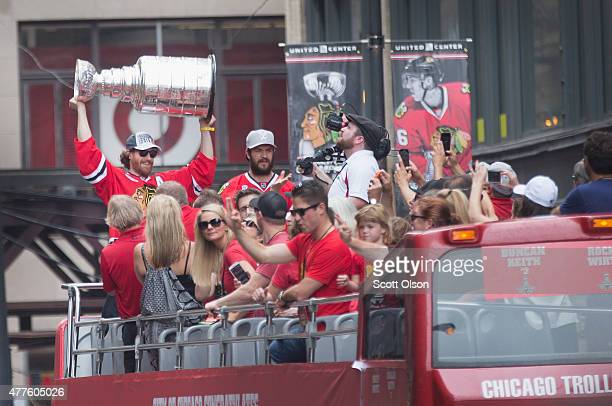 Duncan Keith lifts the trophy as he rides with other members of the Chicago Blackhawks' in a parade through downtown to celebrate their winning of...