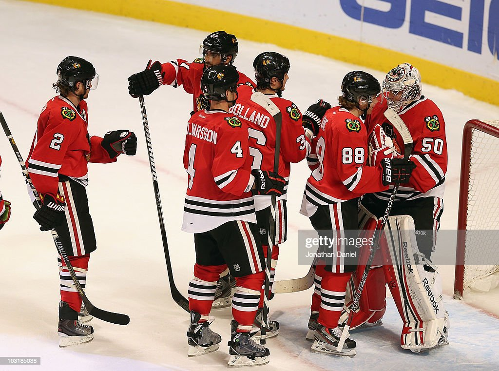 Duncan Keith #2, Niklas Hjalmarsson #4, Dave Bolland #36 and Patrick Kane #88 of the Chicago Blackhawks line up to congratulate goalie Corey Crawford #50 after a win over the Minnesota Wild at the United Center on March 5, 2013 in Chicago, Illinois. The Blackhawks defeated the Wild 5-3.