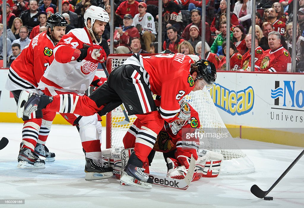 Duncan Keith #2 of the Chicago Blackhawks and Todd Bertuzzi #44 of the Detroit Red Wings scramble toward the puck, next to goalie Corey Crawford #50 of the Blackhawks, during the NHL game on January 27, 2013 at the United Center in Chicago, Illinois.